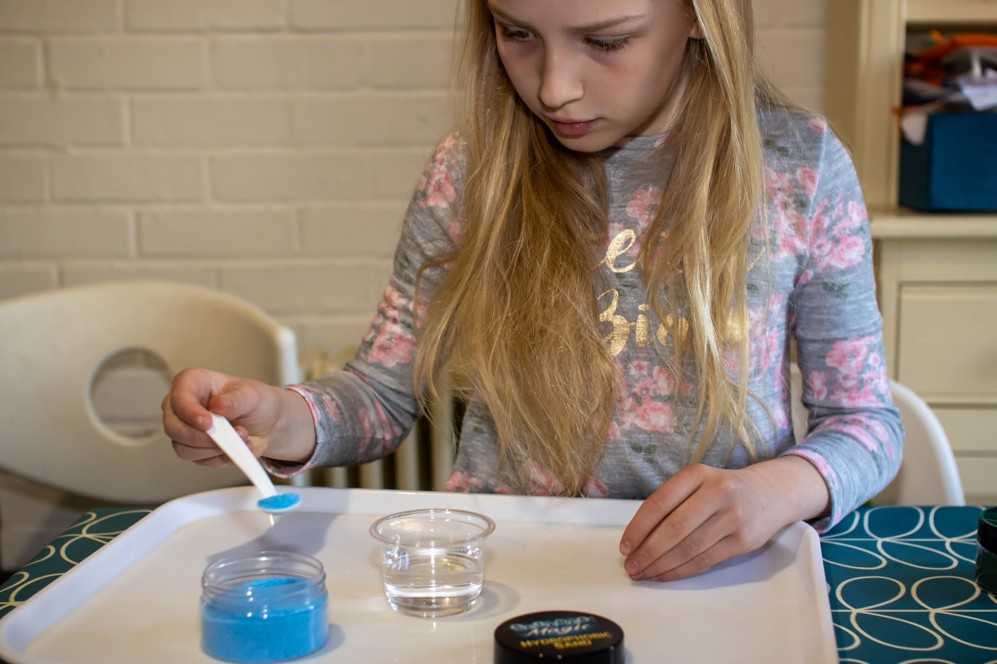 A 9 year old spooning blue hydrophobic sand into a pot of water with total concentration on her face