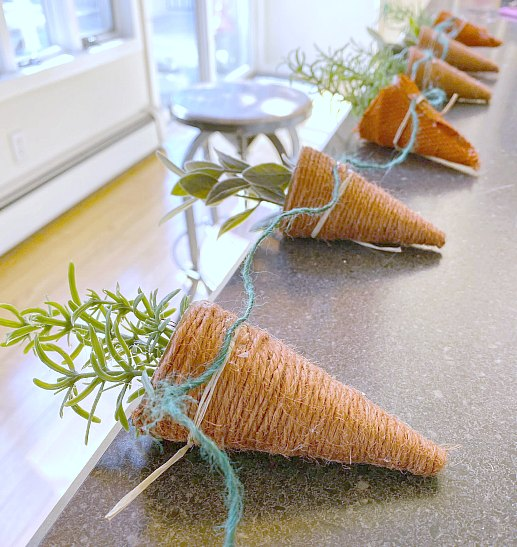 Attaching carrots to a length of jute for hanging