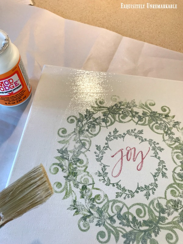 Adding decoupage to canvas with brush over Joy wreath iron on