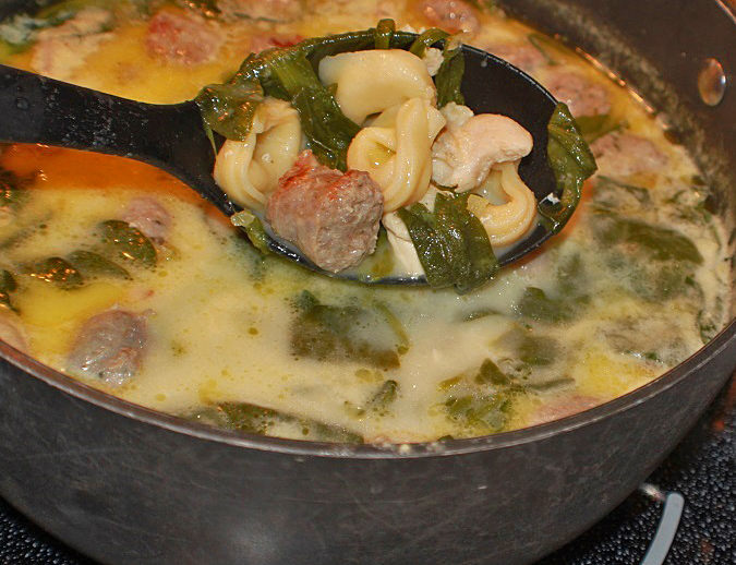 this is a big soup pot of tortellini and sausage soup with spinach