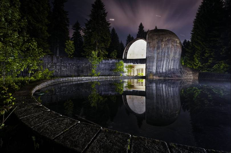 This graceful, curved stone structure in Grmec in Bosnia and Herzegovina is a monument to the revolution and is reflected in a nearby lake.