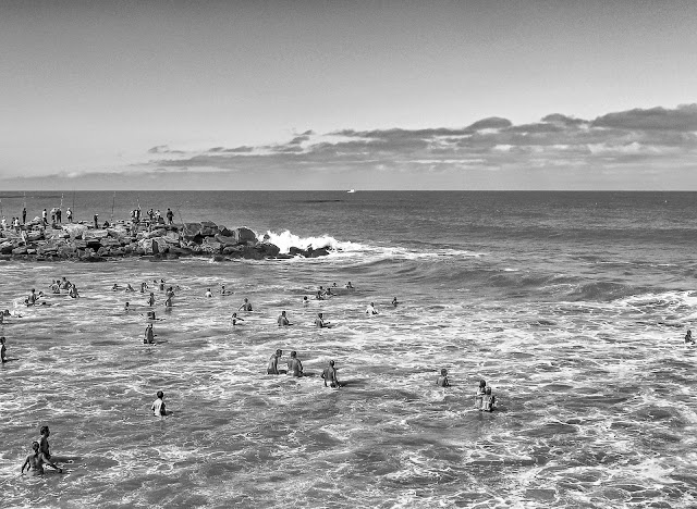 Gente en el agua esperando las olas del mar.