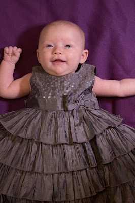 2 month old baby in a grey party dress