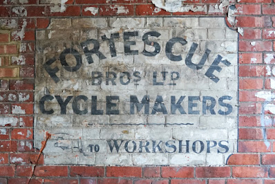 A ghost sign painted on red brick: a white background, with black text reading 'FORTESCUE BROS LTD CYCLE MAKERS. A manicule points left, with the text 'TO WORKSHOPS'