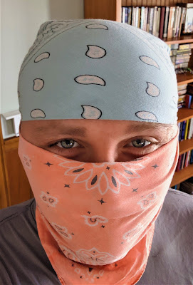 A selfie with a blue bandanna on my head and an orange bandanna covering my face.