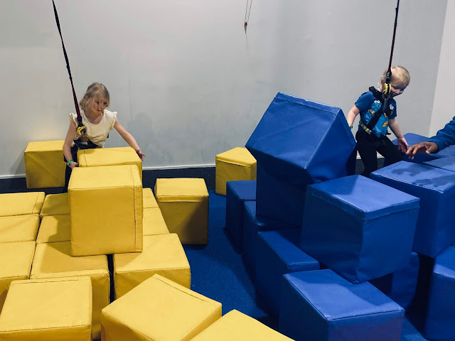 Large blocks in yellow and blue being built up into a tower to climb up