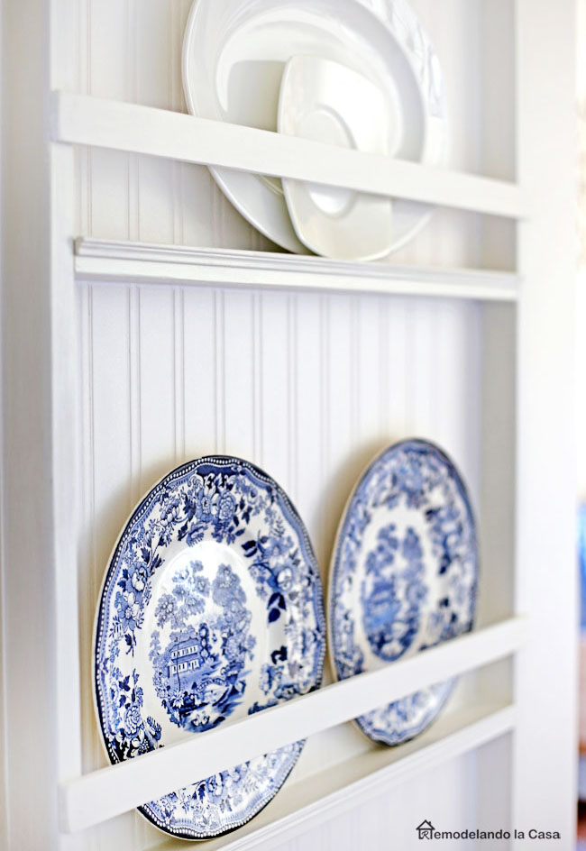 A platter display on the side of fridge with beadboard backing