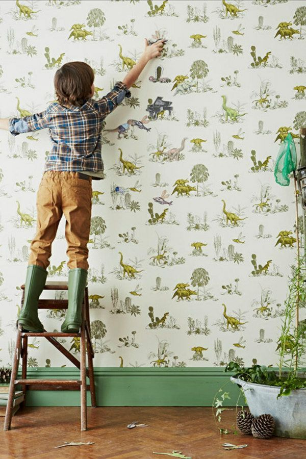 dinosaur magnetic wallpaper with small boy applying magnetized dinos