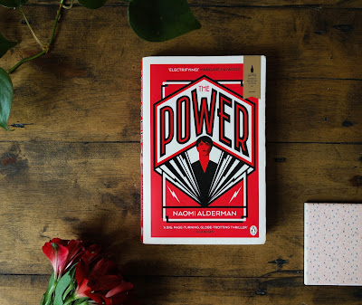 Image of Naomi Alderman's the power with flowers on wooden floor