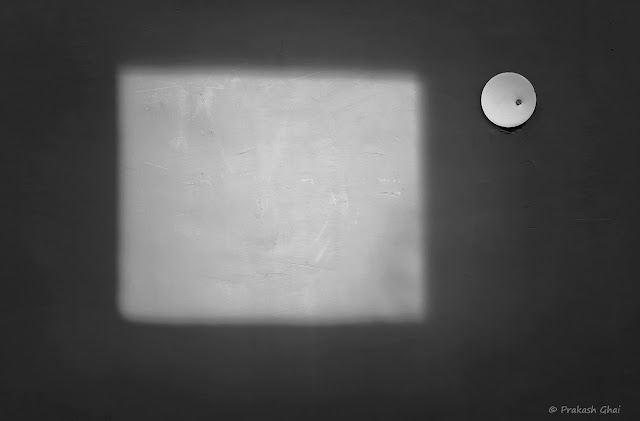 A Black and White Minimal Art Photograph of a Square formed by Light versus a Small White Circle
