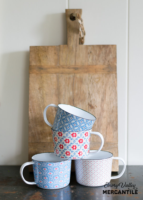 floral enamel mugs in front of a wooden cutting board