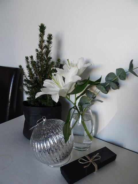 Plantagenin pöytäkuusi, Granitin paperipussi, Annon joulupallo, liljoja lasimaljakossa.