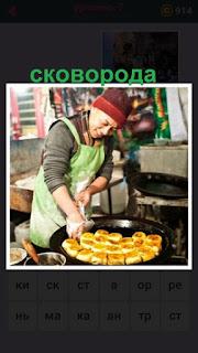 на кухне на сковороде женщина готовит еду, укладывая по кругу