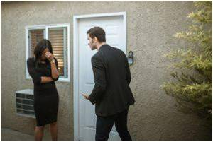 Man in black suit and woman in black dress arguing