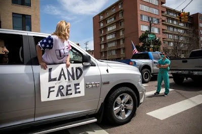 "Nurse with arms crossed staing in middle of road, blocking vechicle with woman leaning out of window with ""Land of the free"" sign"