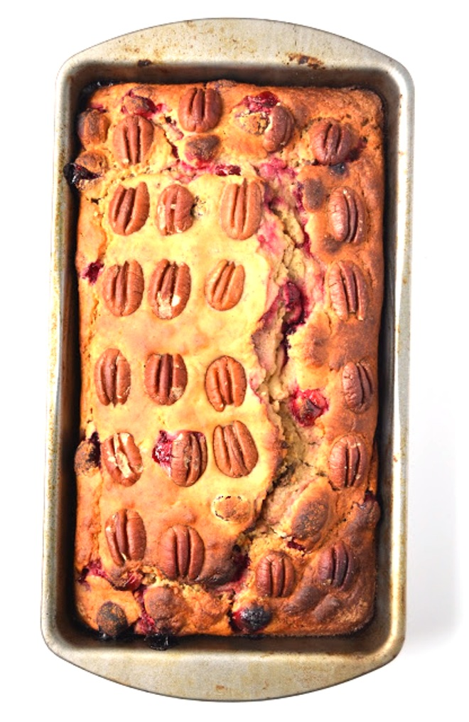 This Cranberry Pecan Banana Bread is lightened up with Greek yogurt, less sugar and whole-wheat flour! Topped with crunchy pecans and loaded with tart cranberries! www.nutritionistreviews.com