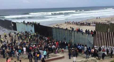 Watch: CHAOS--'Caravan' of illegals climb border fence, cheer 'Gracias, Mexico!'