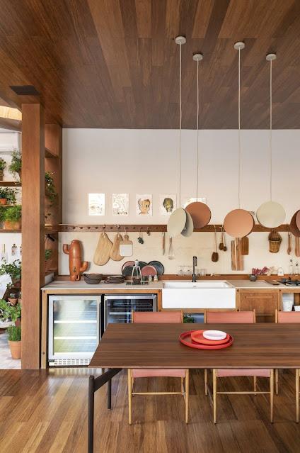 open floor plan galley kitchen with eat-in dining table, under cabinet wine fridge, terra cotta hanging pendant lights, wood peg rack for kitchen utensils