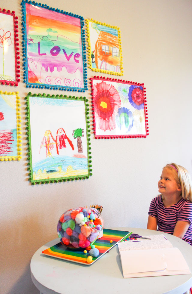 Turn kids art into colorful posters with pom-pom trim frames!