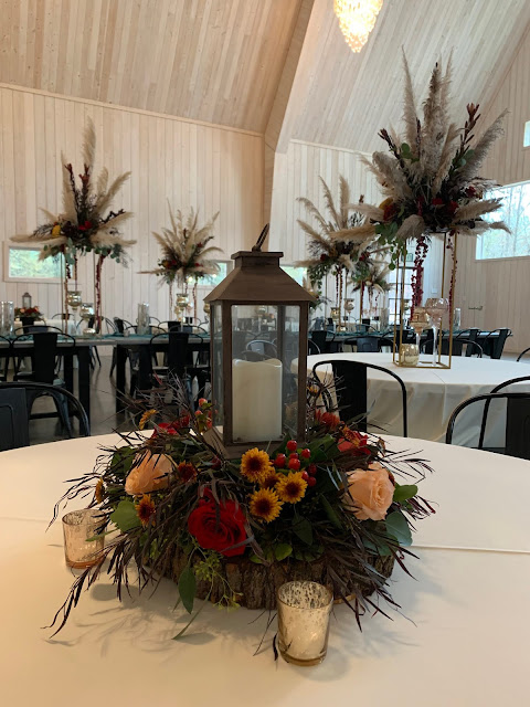 Wedding reception with fall centerpieces in various heights