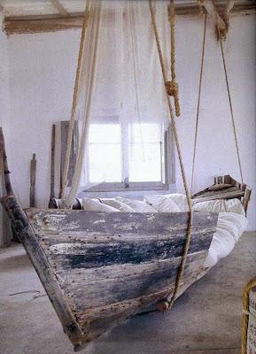 Una cama muy bonita con un toque rústico hecha con un bote viejo.
