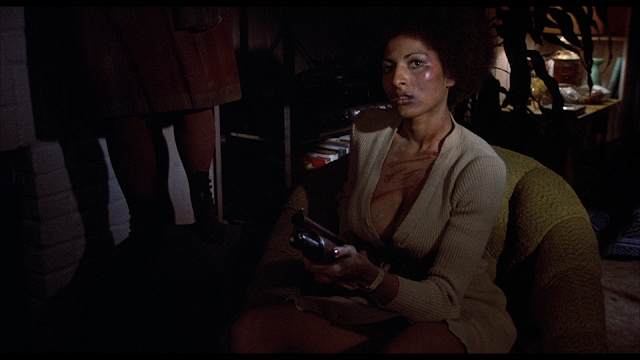 Coffy holds a shotgun at someone offscreen