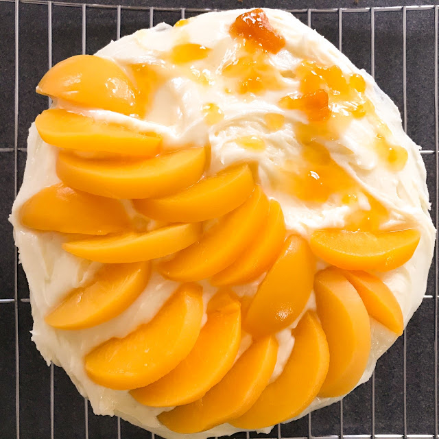 Peaches added to the top of the cake along with jam drizzled onto the top, whilst on a wire tray