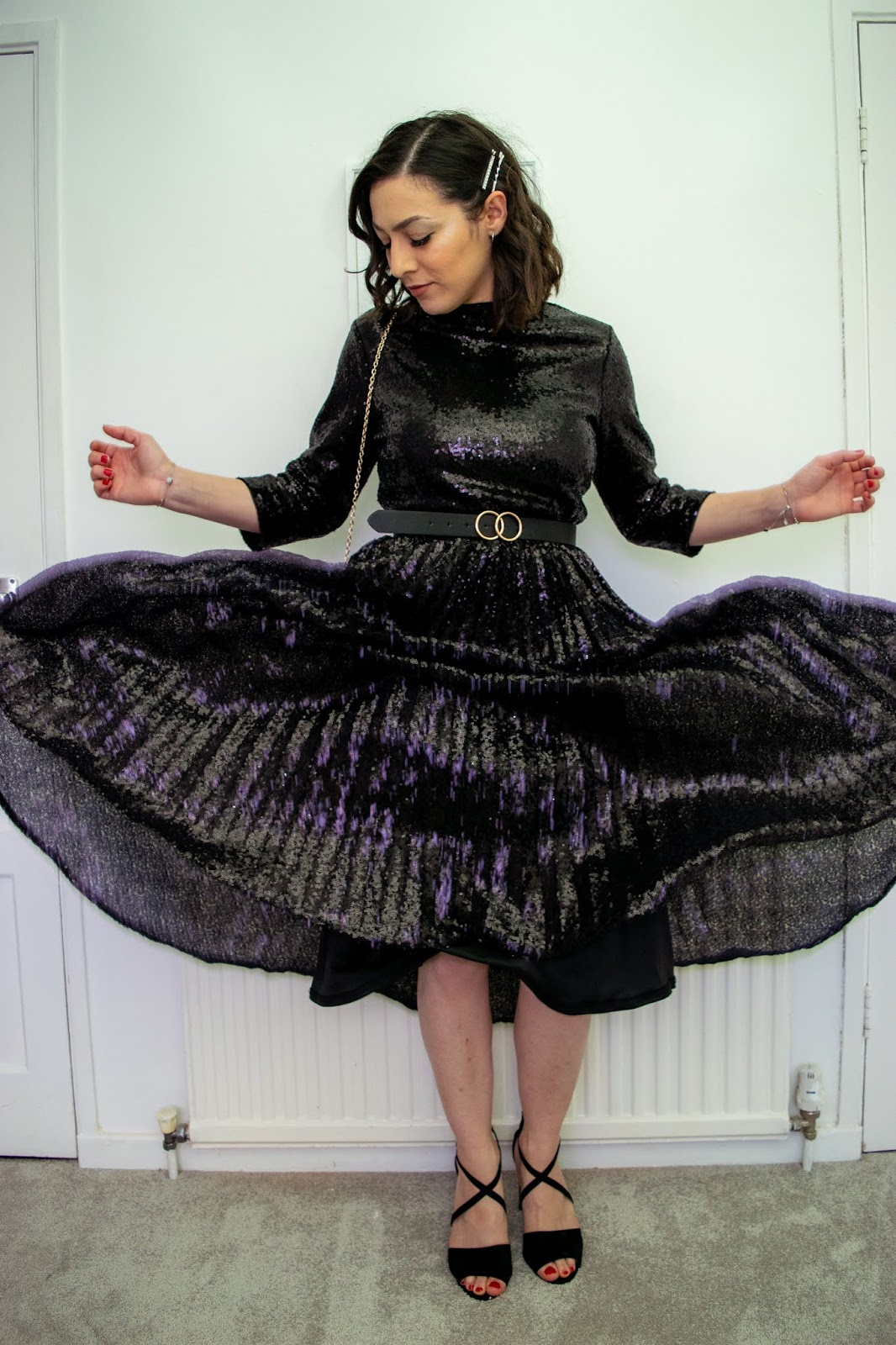 I'm standing with my arms slightly out wearing a black sequin pleated dress that has been caught moving mid-air.