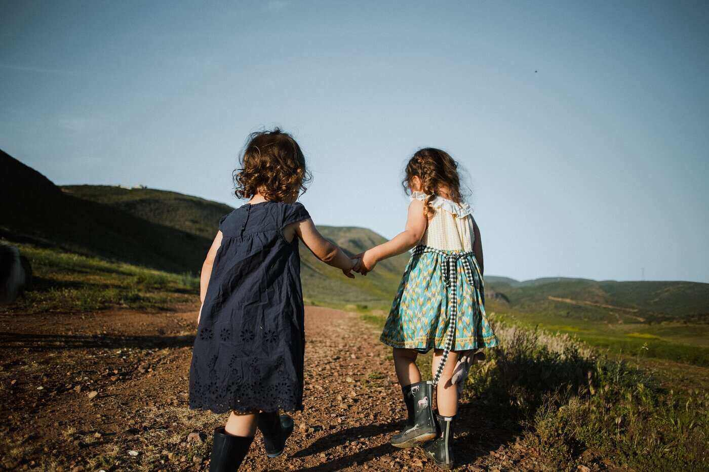 two girls holding hands going up mountain path - clothing your kids