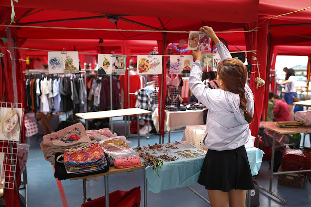 A woman putting items on display at her outdoor selling booth.