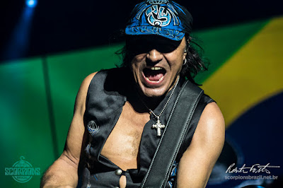 Matthias Jabs playing guitar on stage, opening his mouth as he was screaming, Behind him there is a projection of a Brazilian flag.