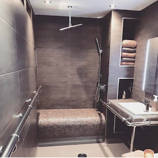 Dark grey/brown tiled walls and floors with tiled bench and hoist above shower.