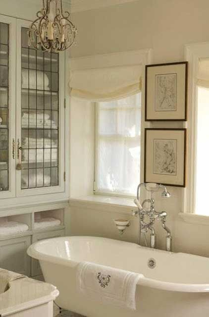Beautiful vintage style farmhouse bathroom with clawfoot tub and glass front cabinet