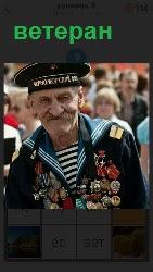 стоит пожилой ветеран с медалями на груди в форме моряка