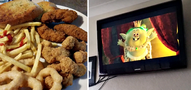 Fried chicken, fries and onion rings and Trolls on the TV