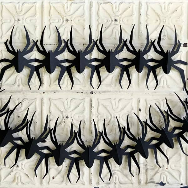 pair of papercut black spider garlands