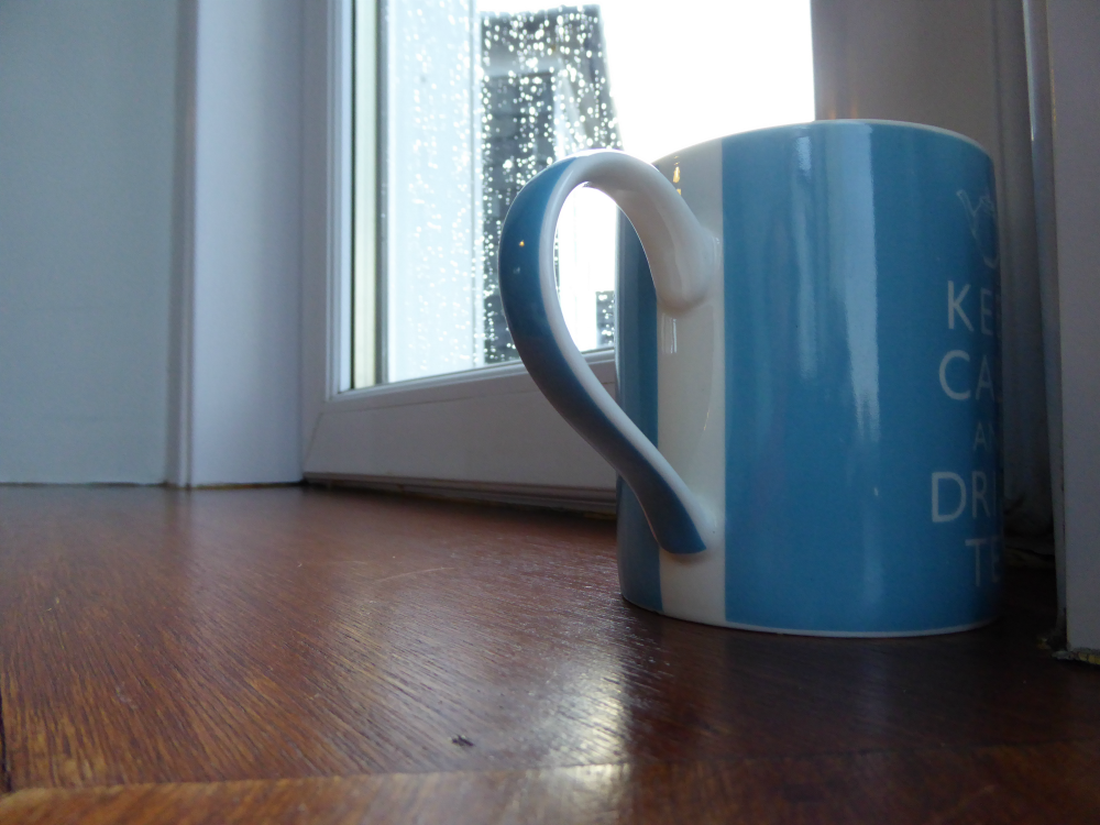 Cup of tea set against rainy window