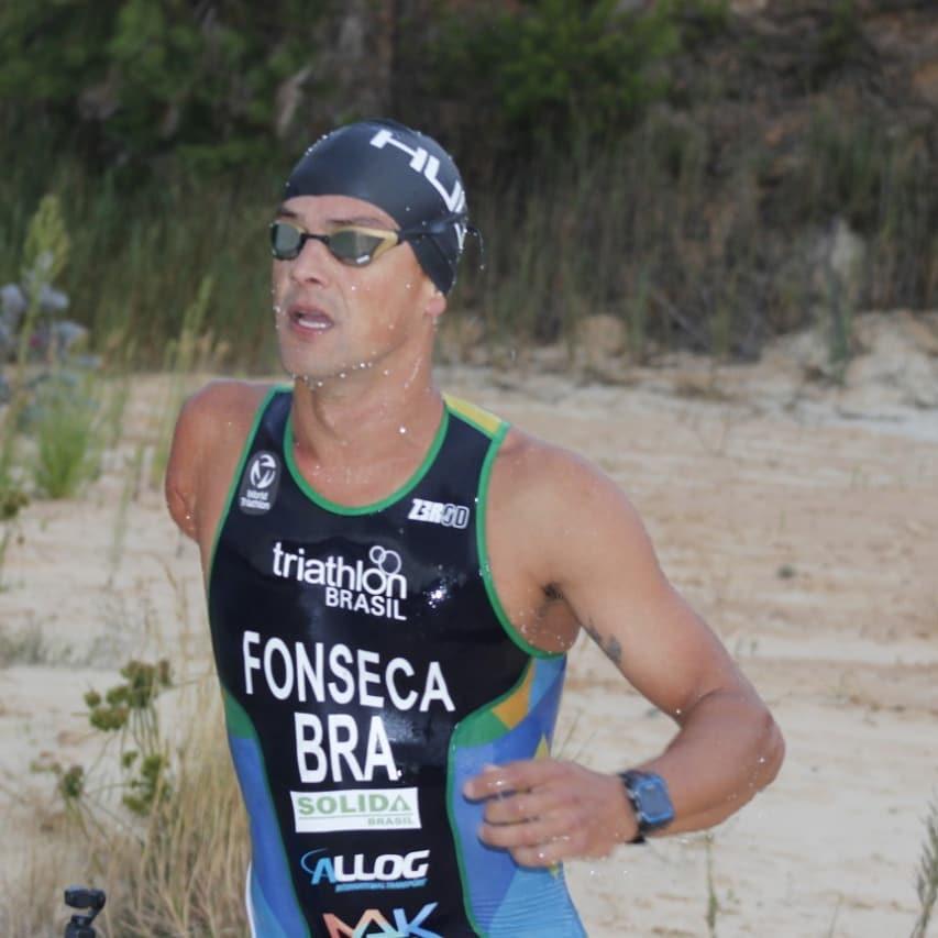 Jorge Fonseca de óculos escuro, touca preta e uniforme preto com detalhes em branco, azul e verde, disputando uma competição
