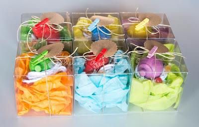 Peonzas de madera empaquetadas en cajas de acetato sobre papel de seda con detalle de etiquetas y pinzas
