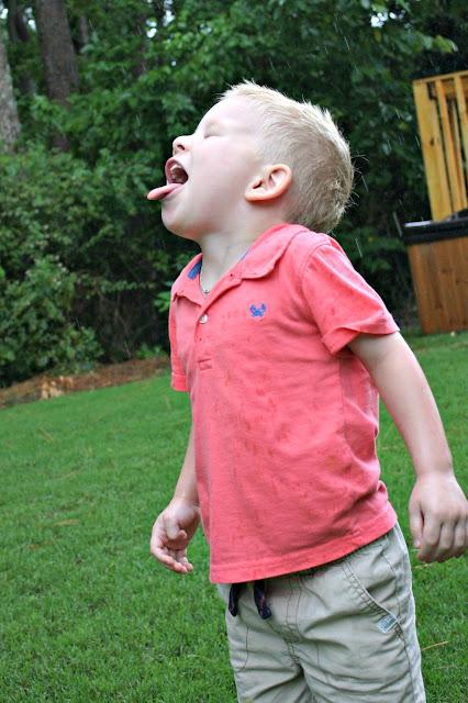 Boy catching rain on his tongue
