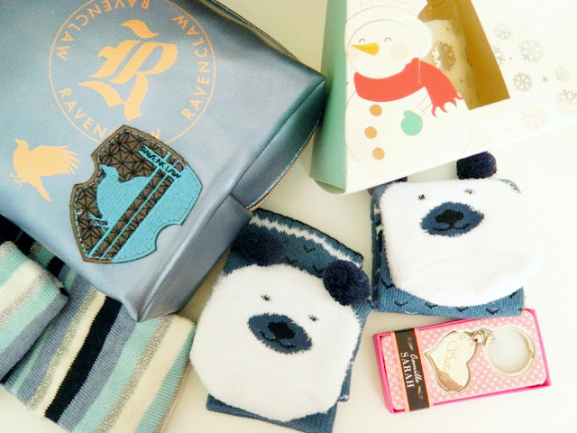 a photo showing christmas socks and candle, a silver heart keyring and a harry potter ravenclaw makeup bag,