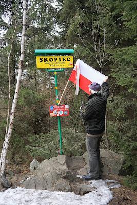 Na szczycie Skopca. Do słupka przymocowana flaga Polski z szarfą ku pamięci Wincentego Witosa.