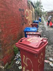 overflowing bins in an alleyway