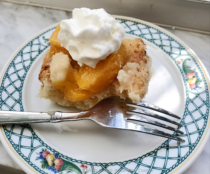 This is a homemade dumplings batter sweetened with syrup using peaches and topped with whipped cream on a fruit lenox china dish and fork sitting on a window sill