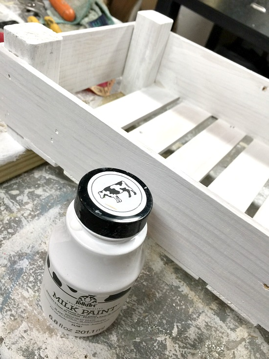Painting a wooden crate with white milk paint