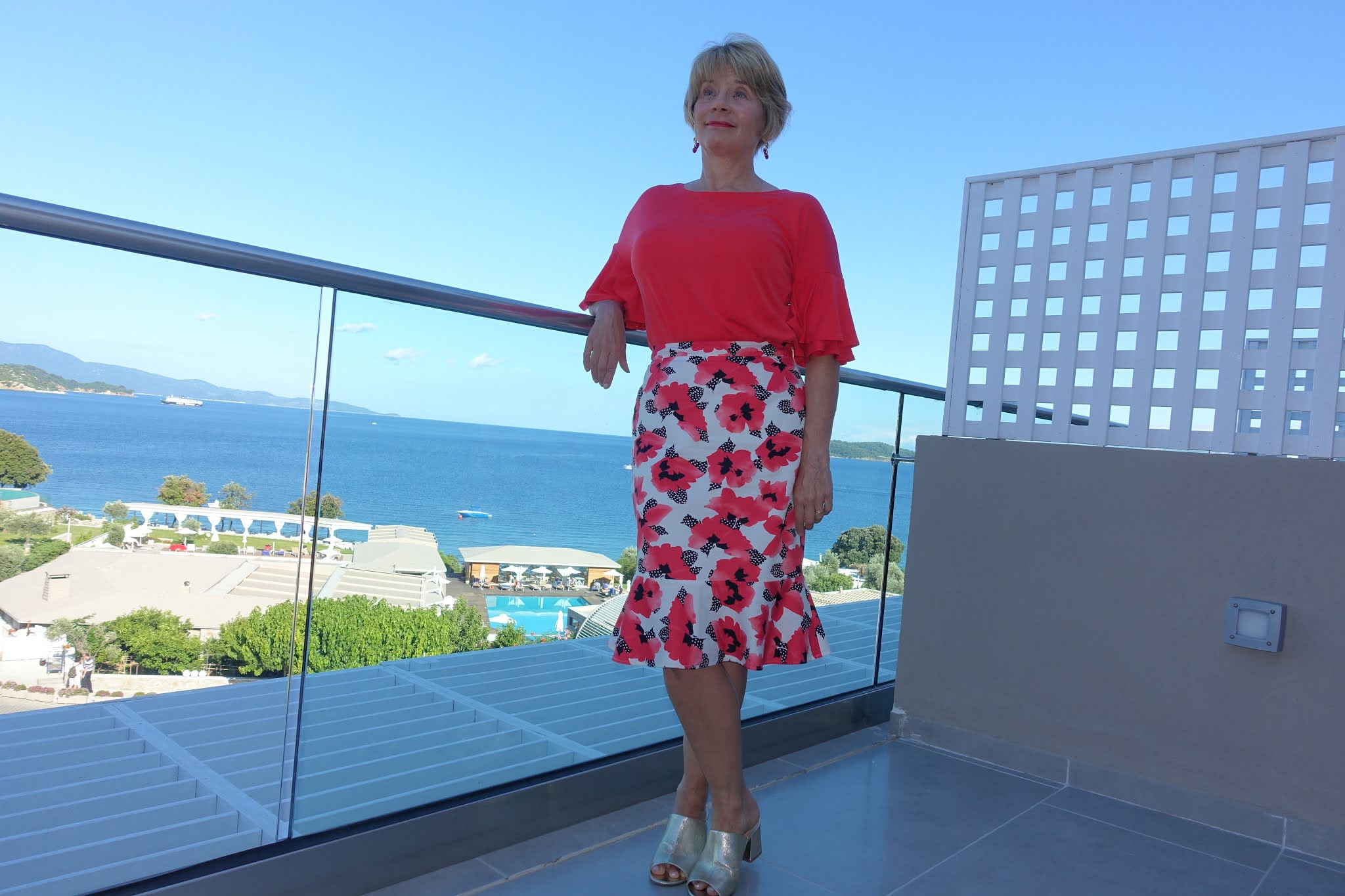 Gail Hanlon in Skiathos overlooking Vasilias beach, wearing a red and white poppy skirt, red top with statement sleeves and gold mules