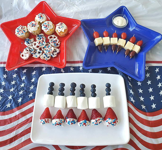 these are 3 filled patriotic red white and blue foods using strawberries, blueberries, marshmallows for a memorial day or 4th of july party food theme. There are tomatoes with cubed mozzarella along with kalamata olive skewers also