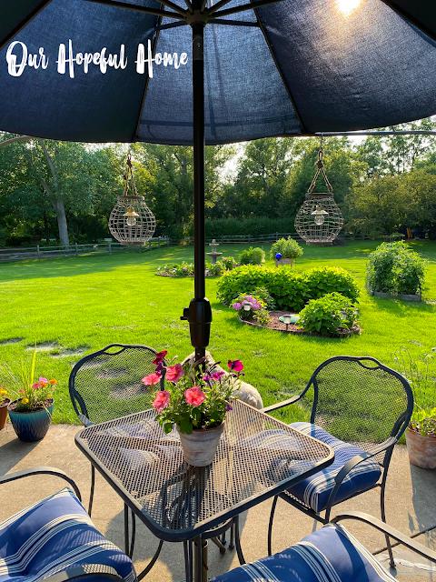 metal patio table blue umbrella petunias