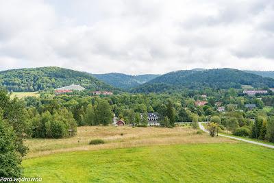 """Wysowa Zdrój: w centrum kadru na linii horyzontu Kozie Żebro, nieco z prawej lekko wypukła Jaworzynka; widzimy też charakterystyczny budynek sanatorium """"Biawena"""", poniżej park zdrojowy"""