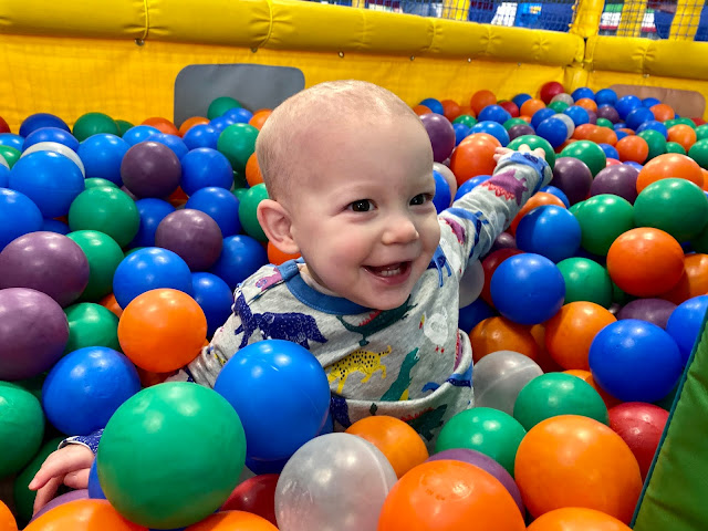 a one year old boy in a ball pool at soft play